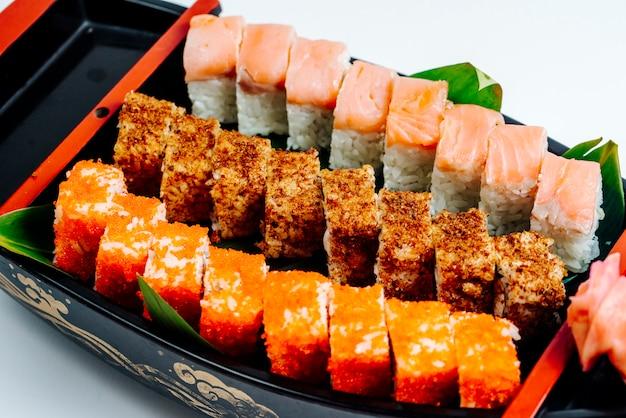 Sluit omhoog van sushi met hete en koude broodjes worden geplaatst dat