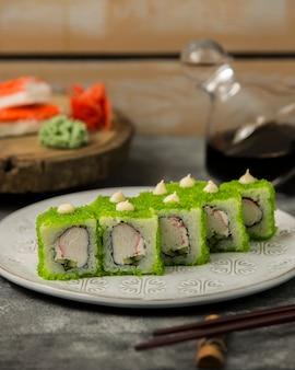 Sluit omhoog van sushi met krabstokken worden geplaatst, komkommer, in groene tobiko worden behandeld die