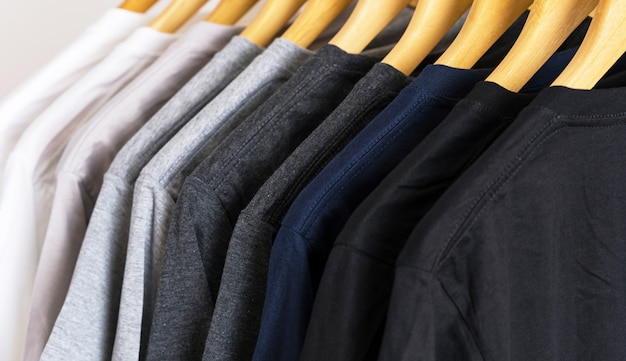 Sluit omhoog van t-shirts op hangers, kleding