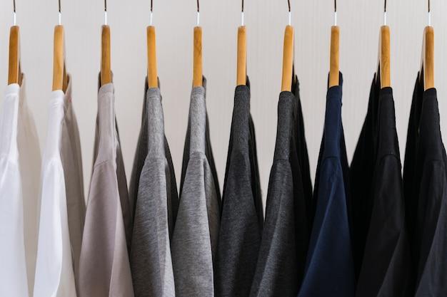 Sluit omhoog van t-shirts op hangers, kledingsachtergrond