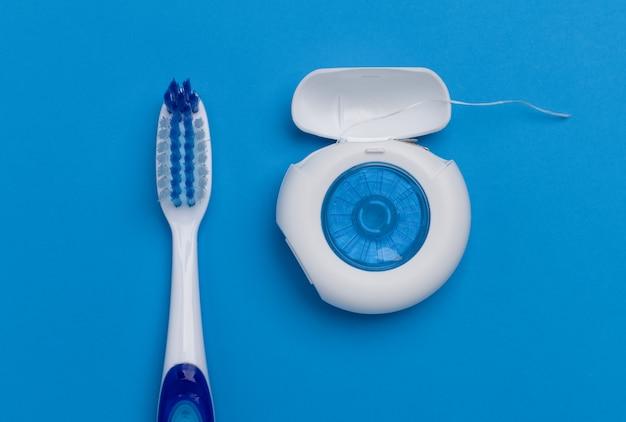 Sluit omhoog van tandenborstel en tandzijde op blauwe achtergrond