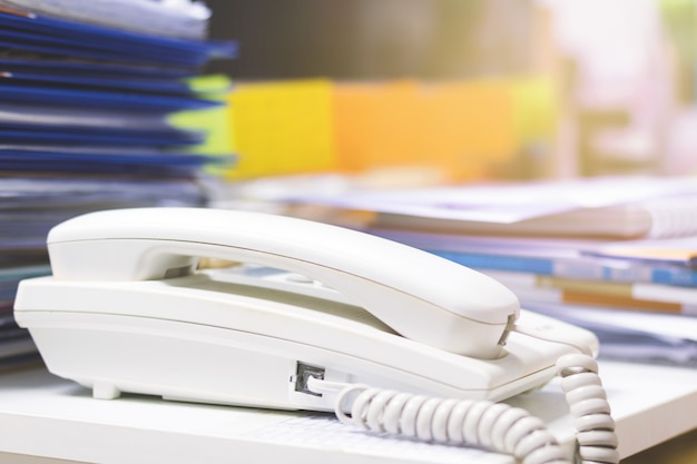 Sluit omhoog van telefoon en veel onvolledige documenten op bureau.