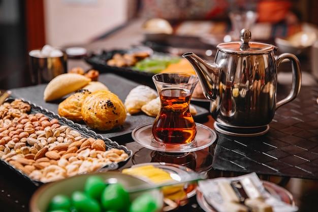 Sluit omhoog van theepot en glas met zwarte thee die voor theeopstelling wordt gediend