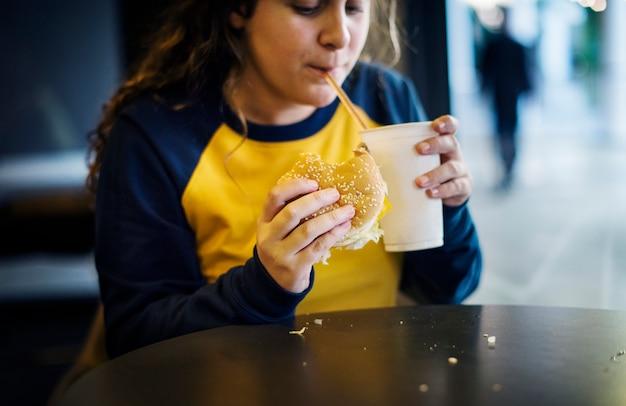 Sluit omhoog van tiener die het concept van de hamburgerzwaarlijvigheid eet