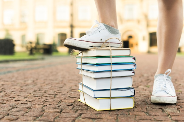 Sluit omhoog van tiener die op boeken stapt