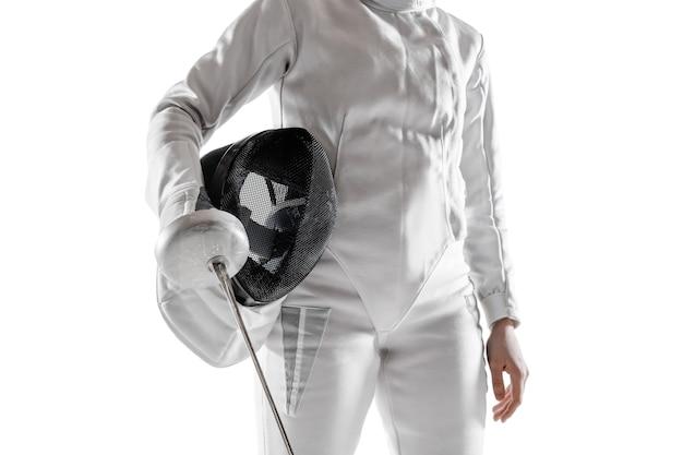 Sluit omhoog van tienermeisje in het schermen kostuum met in hand zwaard dat op witte achtergrond wordt geïsoleerd.