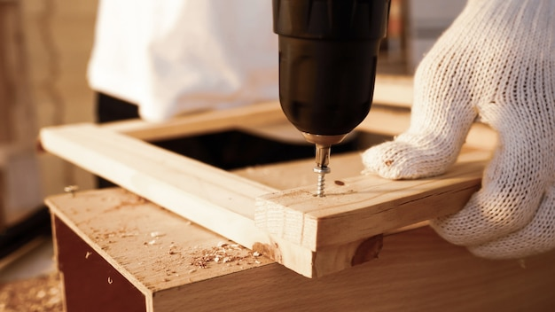 Sluit omhoog van timmerman gebruikend boor om stukken van raad bij plaats te schroeven.