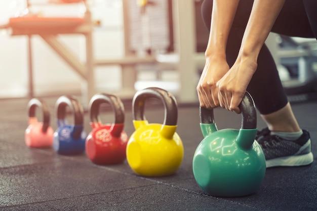 Sluit omhoog van training van de sport de jonge vrouw met kettlebell in gymnastiek