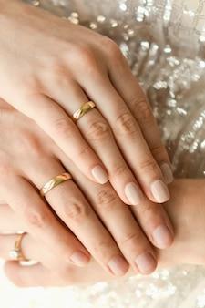 Sluit omhoog van trouwringen op handen van pasgetrouwden. handen van de bruid en bruidegom