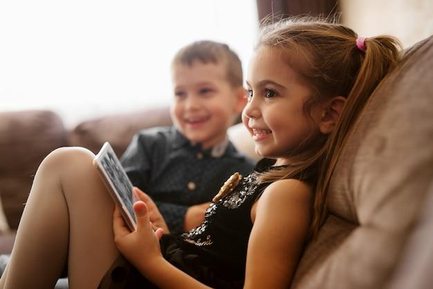 Sluit omhoog van twee gelukkige aanbiddelijke kleine peuterkinderen die op de bank zitten en aan hun ouders glimlachen.