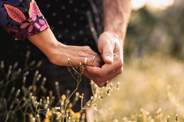 Sluit omhoog van twee jonge volwassenen die handen in het midden van een weide houden. de bloemen staan in bloei.