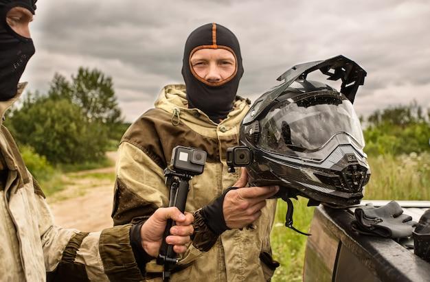 Sluit omhoog van twee mensen die in openlucht bivakmutshelmen en motorfietsuniformen dragen.