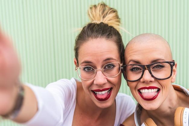 Sluit omhoog van twee vriendenmeisjes die een selfie in openlucht nemen.