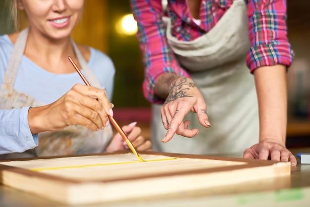 Sluit omhoog van twee vrouwen die in art studio schilderen