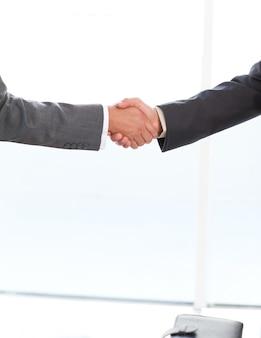 Sluit omhoog van twee zakenlieden die hun handen schudden die zich in het bureau bevinden