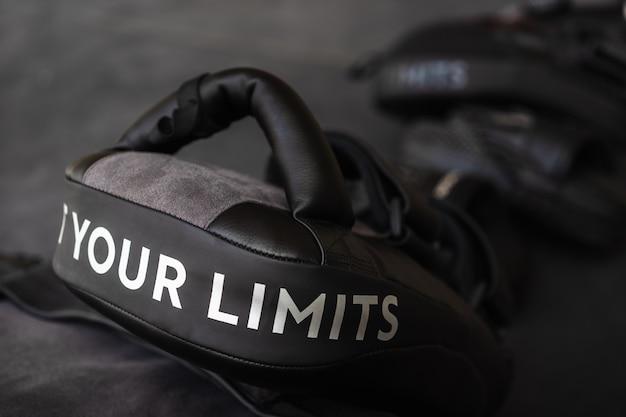 Sluit omhoog van uw grenzenwoord op het zwarte boksen en schoppen oefenblok.