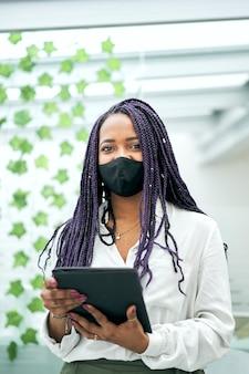 Sluit omhoog van van portret van een onderneemster die een tablet gebruikt die gezichtsmasker draagt