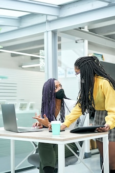 Sluit omhoog van van twee jonge vrouwelijke arbeiders die gezichtsmasker dragen tijdens het werken op laptop