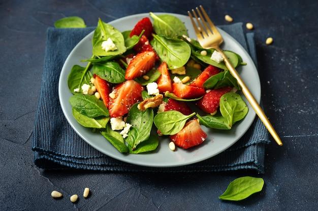 Sluit omhoog van vegetarische slalade met aardbeien, feta-kaas, spinazie en noten