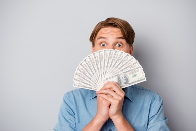 Sluit omhoog van verbaasde funky kerel wint casino loterij jackpot verbergt zijn gezicht geldventilator