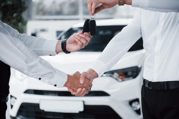 Sluit omhoog van verkoopmanager in zwart kostuum die de auto aan de klant verkopen.