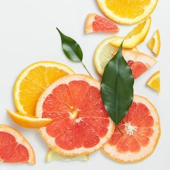 Sluit omhoog van verse citrusvruchtenplakken met blad op witte oppervlakte