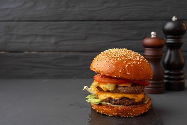 Sluit omhoog van verse smakelijke hamburger tegen zwarte achtergrond
