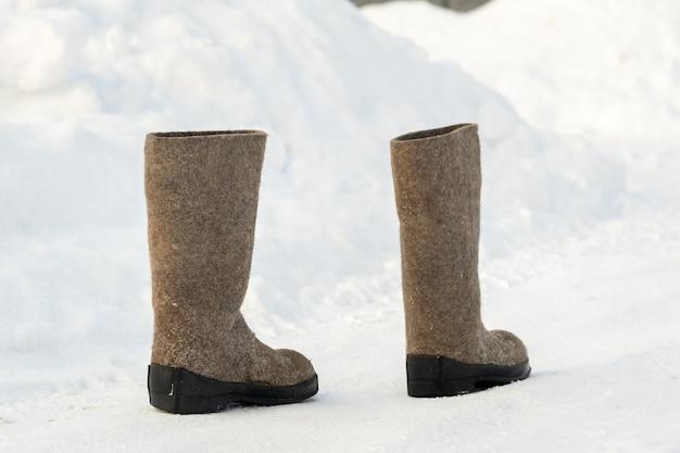 Sluit omhoog van vilten laarzen die zich in de sneeuw bevinden.