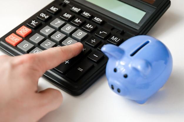 Sluit omhoog van vinger drukt de calculatorknoop dichtbij spaarvarken