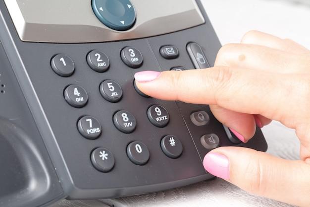 Sluit omhoog van vinger het kiezen om in bureau te telefoneren