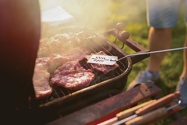 Sluit omhoog van vlees bij de barbecuegrill.