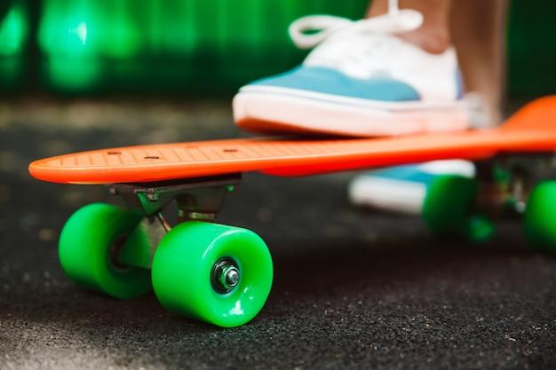 Sluit omhoog van voeten ritten van meisjessneakers op oranje stuiverskateboard op asfalt