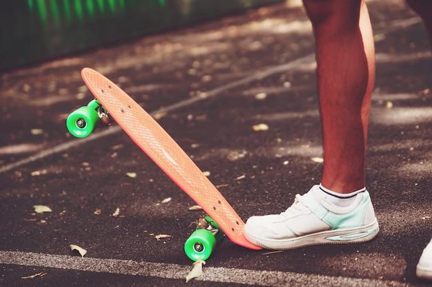 Sluit omhoog van voeten ritten van mensentennisschoenen op oranje stuiverskateboard op asfalt