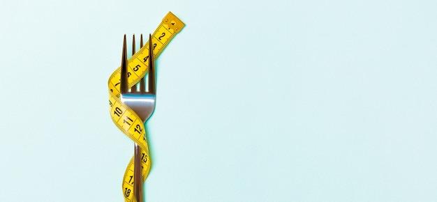 Sluit omhoog van vork die met meetlint op blauw wordt verpakt