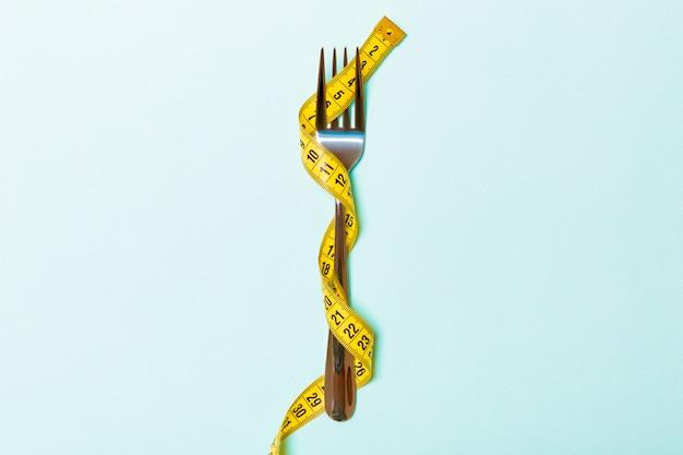 Sluit omhoog van vork die met meetlint op blauwe achtergrond wordt verpakt.