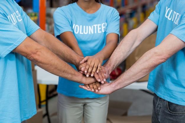 Sluit omhoog van vrijwilligers die bij handen aansluiten zich