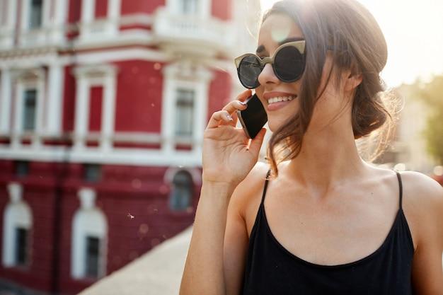 Sluit omhoog van vrolijke aantrekkelijke kaukasische vrouw met donker haar in zonnebril en zwarte kleding sprekend met vriend telefonisch, lopend naar huis, die gelukkige emotie met dichte persoon delen.