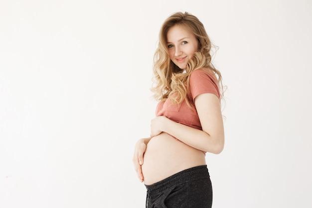 Sluit omhoog van vrolijke jonge knappe zwangere moeder met lang blonde haar in vrijetijdskleding houdend buik met handen