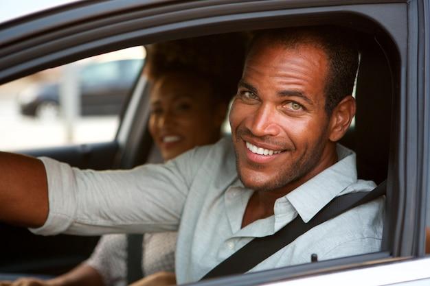 Sluit omhoog van vrolijke man en vrouw in auto op wegreis