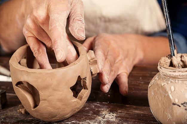 Sluit omhoog van vrouw die aardewerk maakt