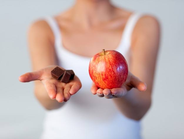 Sluit omhoog van vrouw die chocolade en appelnadruk op appel tonen