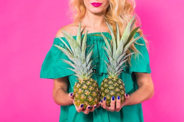 Sluit omhoog van vrouw die een ananas op roze houdt