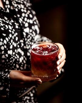 Sluit omhoog van vrouw die een glas cocktail houdt