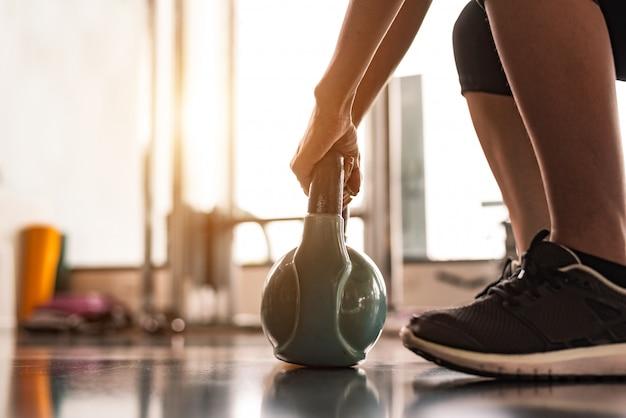 Sluit omhoog van vrouw die kettlebell zoals domoren in de gymnastiek van de geschiktheidssportschool opheffen opleiden