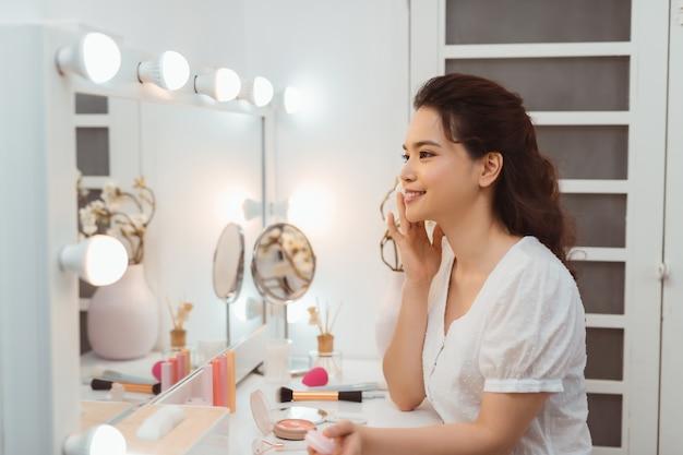 Sluit omhoog van vrouw die van de glimlach de aziatische schoonheid hydrateert door katoen te reinigen en kijk spiegel