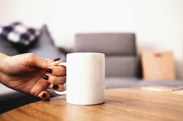 Sluit omhoog van vrouw die verse arabica van de ochtendkoffie van een lijst nemen.