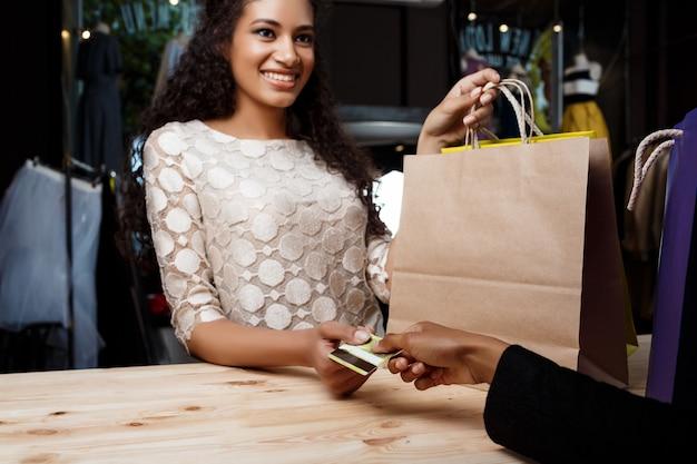 Sluit omhoog van vrouw die voor aankopen in winkelcomplex betalen