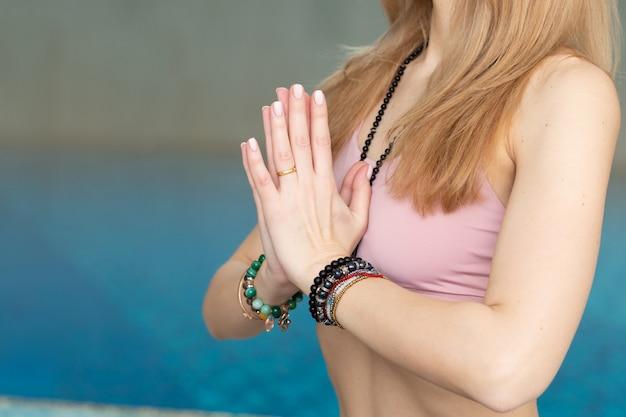 Sluit omhoog van vrouw die yoga doen stelt, handengebaar dichtbij zwembad
