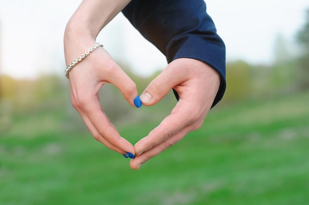 Sluit omhoog van vrouw en man handen die hartvorm tonen
