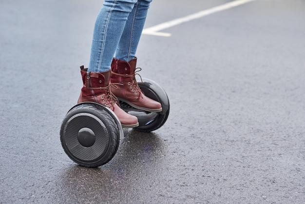 Sluit omhoog van vrouw gebruikend hoverboard op asfaltweg. voeten op elektrische scooter buiten
